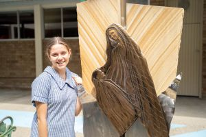 All Saints Catholic College History and Charism - student standing next to Virgin Mary statue