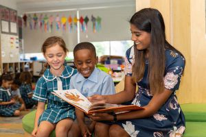 All Saints Catholic College Learning Approach - teacher reading a book to students