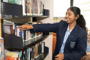 All Saints Catholic College Library - student looking at books in the library