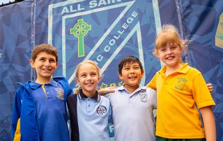 All Saints Catholic College News and Events students in front of school emblem