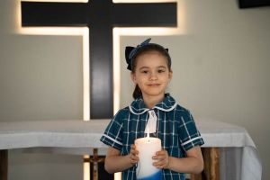 All Saints Catholic College Our Parish - student holding a candle