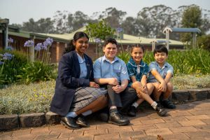 All Saints Catholic College Outreach - students sitting in front of school garden
